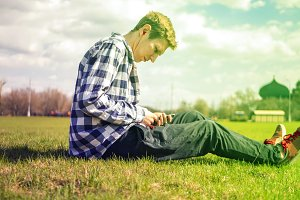 young man listenning to the music in the earbuds during summer sunny day lying on the grass in the park