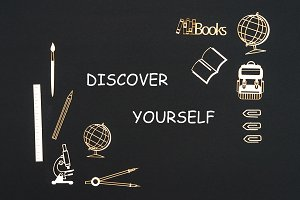School supplies placed on black background with text discover yourself