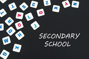 english colored square letters scattered on black background with text secondary school