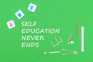 text self education never ends, from above wooden minitures school supplies and abc letters on green background