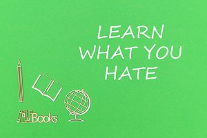 text learn what you hate, school supplies wooden miniatures on green background