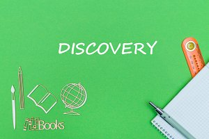 text discovery, school supplies wooden miniatures, notebook on green background