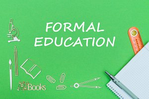 text formal education, school supplies wooden miniatures, notebook with ruler, pen on green backboard