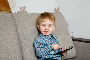 Boy sitting on sofa with smartphone