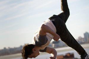 Young male acrobatic sportsman performs tricks jumps in front of skyline