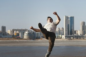 Young male parkour sportsman performs acrobatic jumps in front of skyline