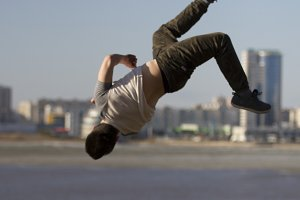 Young man parkour sportsman performs back tricks in front of skyline