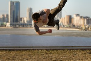 Young man fighter performs acrobatic kick in front of skyline