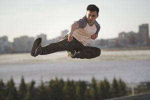 Young man fighter performs flying kick in front of skyline
