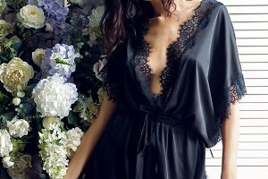 sexy brunette girl in a silk black robe stands