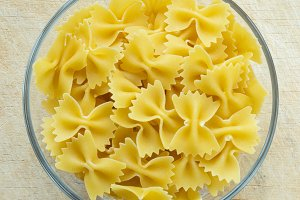 farfalle macaroni pasta in a glass bowl on a wooden table texture background, in the center close-up with the top.