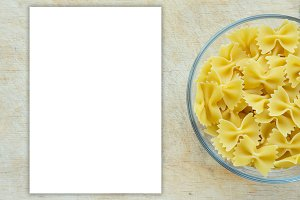 farfalle macaroni Pasta in a glass cup on a wooden table textured background with a side. Close-up with the top. White space for text and ideas.