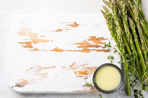fresh green asparagus and old white wooden board