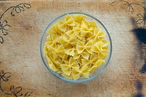 farfalle macaroni pasta in a glass bowl on a wooden cutting board, texture background, in the center with the top.