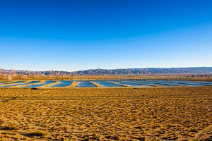 Windmills farm and water reservoirs along a highway in Mojave desert