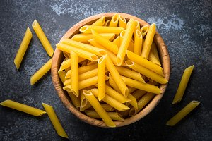Pasta penne  in wooden bowl on black.