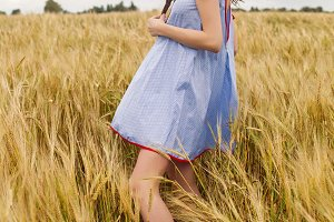 woman in a blue light dress stands in a field