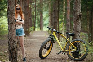 Young caucasian woman on bike in the woods
