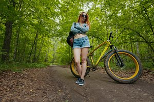 Attractive young woman standing near the tree in the woods with bike