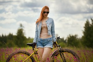 Happy young woman with bike in a summer flower field