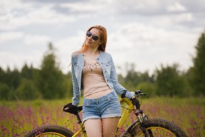 Attractive young woman in sportswear in a flower field with bike