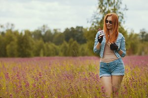 Attractive sexy red-haired model in a summer field with flowers