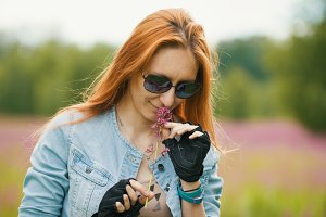 Portrait of attractive young woman in glasses with flower outdoors