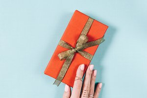 Female hand and red gift box