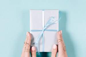 Gift box with bow in female hands