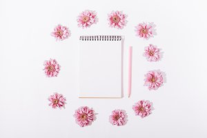 Pink flowers around a notepad