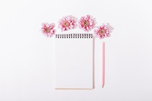 Notepad with a pencil and pink flowe