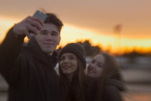 Three friends doing selfie for a walk at the sunset