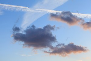 Blue sky and clouds. Plane flying through clouds leaving vapour trails.