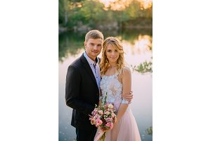 portrait of newlywed couple on the background of a lake at sunset