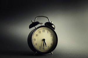 Vintage clock against isolated dark background