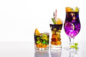 Selection of colorful festive drinks, alcoholic beverages and cocktails in elegant glasses on white