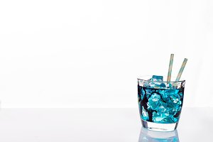 cocktail glass with blue alcoholic drink , close-up isolated on white.