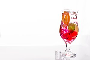 Pink and red Fresh colorful exotic alcoholic cocktail with lemon and ice on white