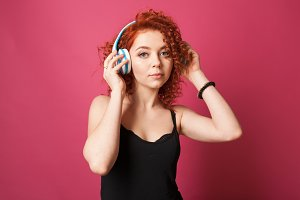 curly redhead girl listens to music with headphones. Studio