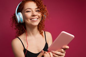 redhead curly girl with a Smartphone in headphones