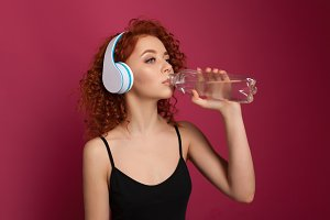 Pretty healthy young woman drinking pure mineral bottled water on a pink background