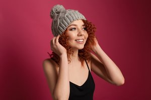 Cute young woman wearing warm winter hat posing in studio