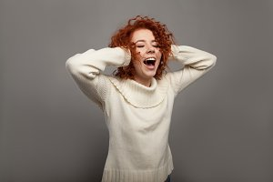 Beautiful redhead curly woman screams in shock