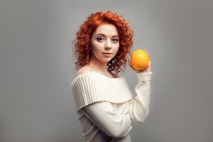 Beautiful redhead curly woman eating Orange
