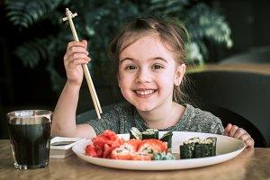 Little cute little girl eating sushi