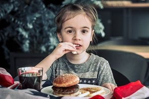 little girl in cafe with burger