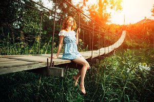 young beautiful girl standing on the bridge over the river.