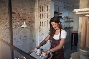 Artisan turning clay on a wheel in her creative studio