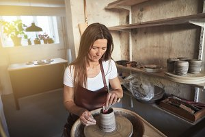 Artisan shaping a vase in her creative pottery workshop