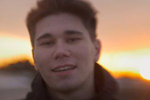 Portrait of young attractive man smiling at sunset